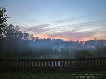 Long view of a house set in a misty sunset sky. Image credit: the auroran sunset
